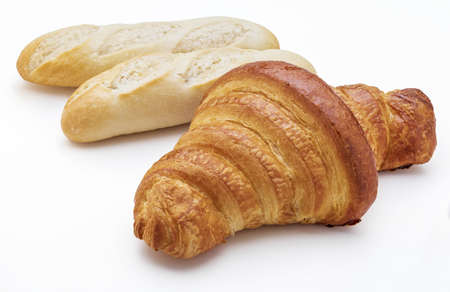 Crispy fresh butter croissant and loaves of bread. Isolated on white background. Фото со стока