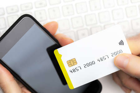 Close-up of online shopper paying with credit cards with smartphone on computer keyboard with copy space. Online shopping.