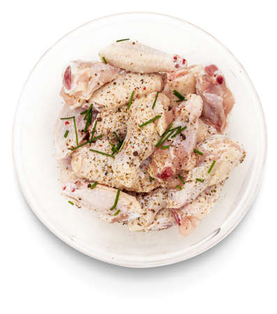 Raw chicken wings marinated with salt, pepper and chives in a bowl isolated on white background.