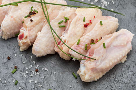 Close-up of raw chicken wings marinated with salt, pepper and chives on a black slate board. Фото со стока