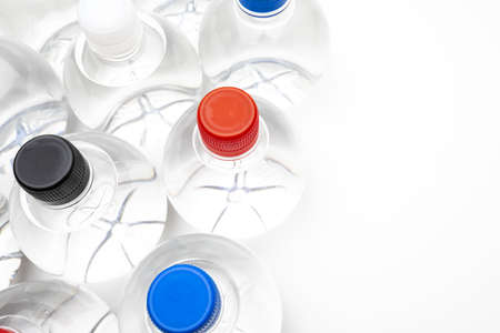 Background of transparent spherical water bottles with colored caps. With copy space. Фото со стока
