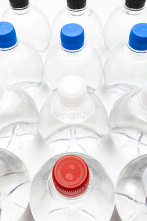 Background of transparent spherical water bottles with colored caps. Фото со стока