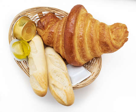 Sweet and salty breakfast. Wicker basket with Croissant, rolls, olive oil and jam. Isolated on white background.