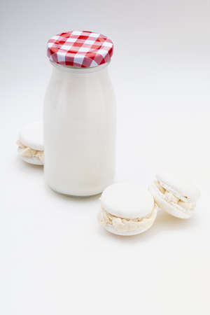 Milk bottle with delicious white macarons. Copy space. Isolated on white background.