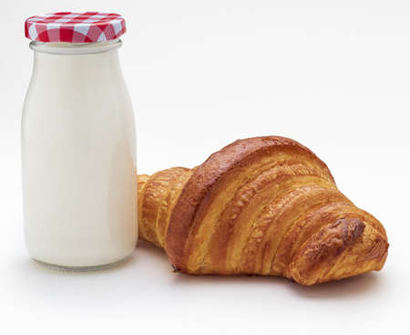 Milk bottle and croissant, Copy space. Isolated on white background.