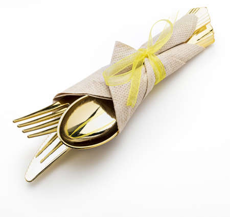 Golden cutlery (knife, fork and spoon) with napkin and bow. Ready for picnic. Isolated on white background.