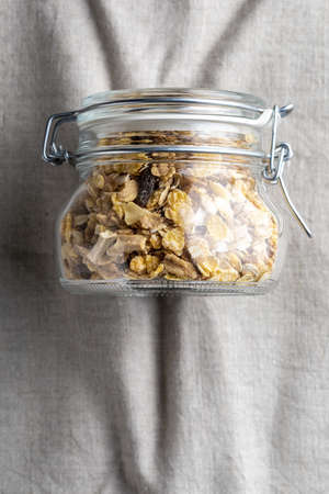 Glass jar with wholegrain breakfast cereals on delicate linen background. Muesli with dried fruits and dried fruits. With copy space. Top view. Reklamní fotografie