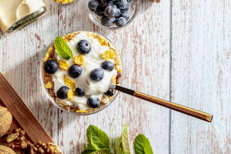 Delicious dessert of blueberries, yogurt and cereals (muesli). Refreshing and healthy breakfast of yogurt, blueberries, dried fruits and dried fruits. With copy space.Top view.