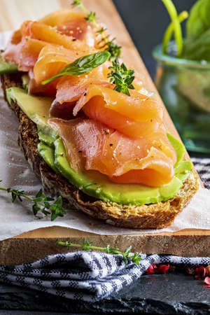 Appetizing and healthy smoked salmon with avocado and vegetables (spinach sprouts, tomatoes, thyme) on toast. Homemade look. Reklamní fotografie
