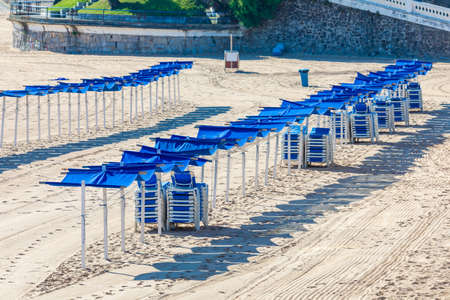 Empty beach, no person. No one on the beach, no tourists or quarantined travelers. With hammocks and blue umbrellas (Spain) Reklamní fotografie