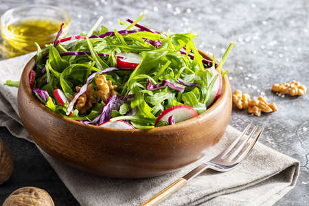 Appetizing and healthy low calorie salad with arugula, radishes, red cabbage and walnuts. In a wooden bowl and homemade look. Mediterranean diet. With Copy space.