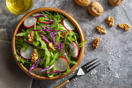 Appetizing and healthy low calorie salad with arugula, radishes, red cabbage and walnuts. In a wooden bowl and homemade look. Top view and copy space.