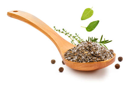 Fine and white salt with fine herbs, with various spices (rosemary, oregano and black pepper) in a wooden spoon (salt varieties collection). Isolated on white background Rustic appearance