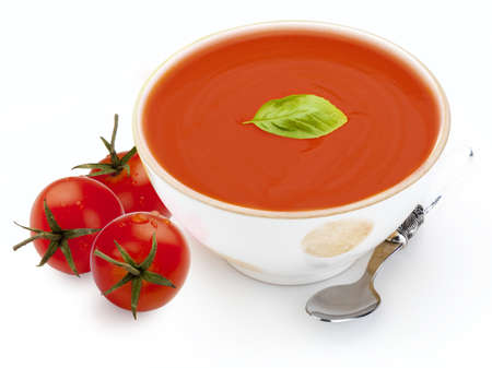 Bowl with tomato soup (gazpacho, tomatoes, basil leaf and spoon. Isolated on white background. Mediterranean diet food composed of tomato, cucumber, peppers, bread, olive oil, bread, garlic, vinegar and fresh basil leaf.
