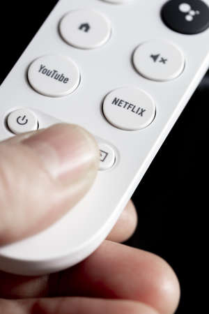 SPAIN - March 3, 2021. Close-up of the Netflix button on the remote control for Chromecast with Google TV in one hand Redakční