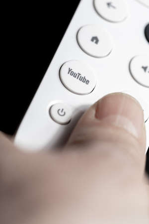 SPAIN - March 3, 2021. Close-up of the Youtube button on the remote control for Chromecast with Google TV in one hand Redakční