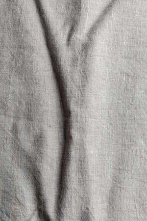 Delicate linen fabric texture. With various folds and wrinkles.Macro close-up. With copy space.