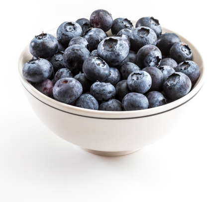 Fresh and raw blueberries with drops of water. In white bowl and ready to eat. Isolated with copy space.