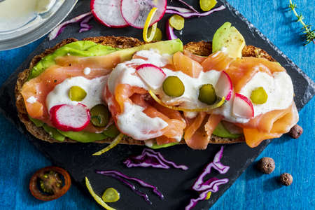 Appetizing and healthy smoked salmon with avocado, vegetables (radish, lemon, red cabbage, pickle) and yogurt sauce on toasted whole wheat bread. Homemade look. Top view. Reklamní fotografie