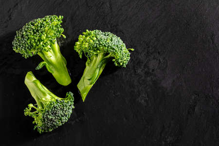 Fresh raw broccoli (Broccoli, brocolli, broccoli, broccoli sprout, brassica oleracea) stalks with water drops on textured slate background. With copy space. Mediterranean diet food.