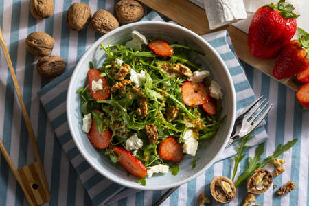 Vegetarian and healthy salad of green, natural, raw and freshly cut arugula (rugula) sprouts and leaves (brassicaceae), with fresh strawberries, walnuts, goat cheese and extra virgin olive oil. Mediterranean diet food. Top view. Reklamní fotografie
