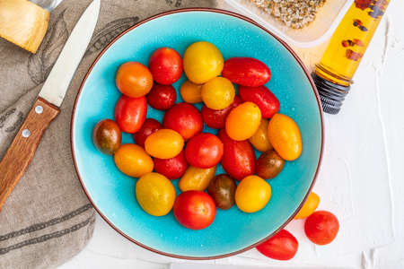 Bowl of colorful cherry tomatoes (red, garnet and yellow), fresh and raw. With water drops Homemade appearance with olive oil and spices. Top View