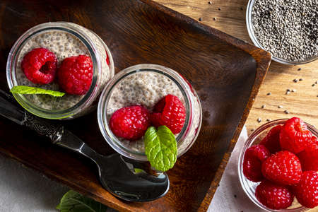 Appetizing, healthy and refreshing chia seed pudding with fresh raspberries, mint leaves and cookies. Vegetarian and vegan food with healthy superfoods. Homemade look. Top view.