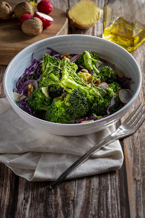 Plate with a healthy vegetarian salad of steamed broccoli, fresh radishes, walnuts, red cabbage, ginger and extra virgin olive oil. Mediterranean diet food. With copy space.
