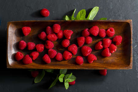 Delicious and appetizing raspberries on an ebony wood tray and spearmint (peppermint, mint) leaves. On black textured background. Top view with copy space. Stock fotó