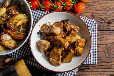 Appetizing stew of pork tenderloin meat cooked in the wok, cut into cubes. With roasted and golden potatoes, garlic, salt, oregano and fresh tomatoes. Homemade look. Top view. Stock fotó