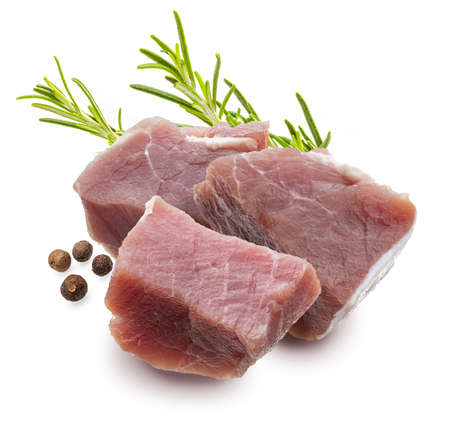 Raw, juicy and fresh chunks (dice shaped) of pork tenderloin. With rosemary leaves and black pepper. Isolated on white background.