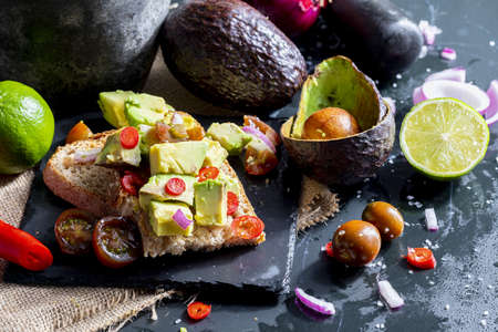 Chunks of avocado, onion, chili and lime juice on toast. Delicious dinner or lunch with healthy plant ingredients. Stock fotó
