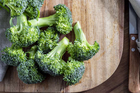 Close-up of raw, fresh broccoli (Broccoli, brocolli, broqui, broccoli brote, brassica oleracea) stalks with drops of water in the preparation process. Top view. With copy space. Mediterranean diet food.