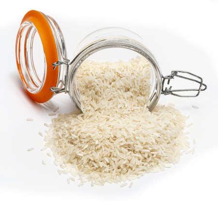 Jar with spilled raw and dry white rice. Isolated on white background.