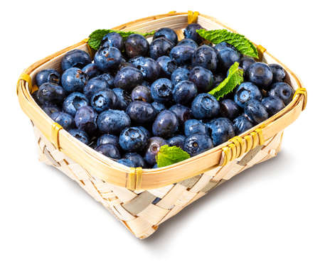 Fresh and raw blueberries with drops of water. In a small wicker basket and green mint leaves. Isolated with copy space.