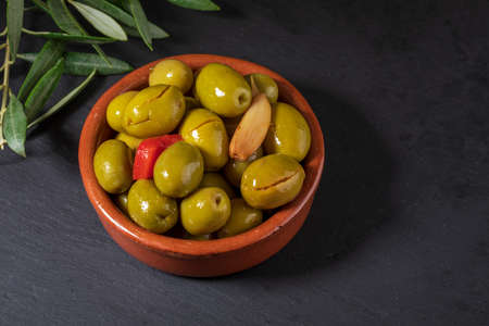 Clay pot with artisan olives (preserved in extra virgin olive oil, vinegar, spices) with red peppers and garlic. Includes leaves of the olive tree. Appetizer concept. On black chalkboard background. Stock fotó