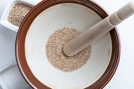 Preparation of gomashio (gomasio - sekihan seasoning) with sesame seeds and salt in Suribachi (Japanese streak mortar). Top view.