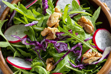 Appetizing and healthy low calorie salad with arugula, radishes, red cabbage and walnuts. In a wooden bowl and homemade look. Macro close-up.