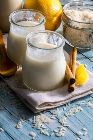 Appetizing rice pudding in glass jars with cinnamon sticks, grains of rice, milk and lemons. Ready to eat !. Homemade look.