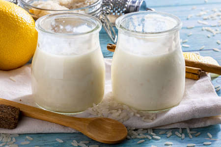 Appetizing rice pudding in glass jars with cinnamon sticks, grains of rice, milk and lemons. Ready to eat !. Homemade look. Front view.