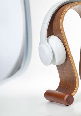 HIFI headphones (High Fidelity) on a wooden omega stand. Isolated on white background.