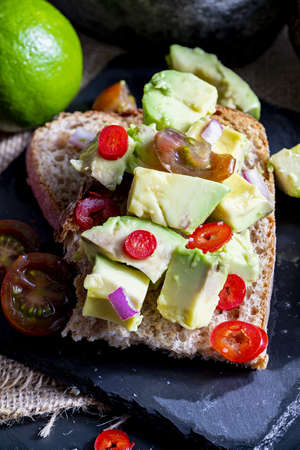 Chunks of avocado, onion, chili and lime juice on toast. Delicious dinner or lunch with healthy plant ingredients. Top view. Stock fotó