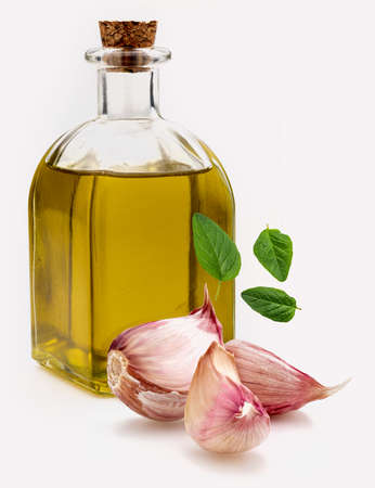 Extra virgin olive oil in a rustic glass bottle with purple garlic and fresh oregano leaves. Ingredients of the Mediterranean diet. Close-up. Isolated on white background