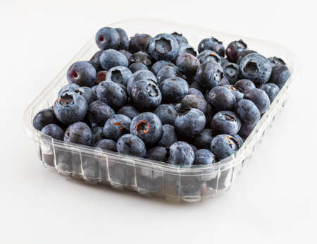 Fresh and raw blueberries with drops of water. In transparent container just bought. Isolated with copy space. Stock fotó