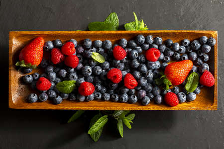 Appetizing variety of forest fruits (strawberries, strawberries, raspberries, blueberries, red berries) on a wooden tray and mint leaves (peppermint, mint). On white textured background. Top view with copy space.