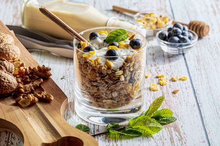 Delicious dessert of blueberries, yogurt and cereals (muesli). Refreshing and healthy breakfast of yogurt, blueberries, dried fruits and dried fruits. With copy space. Stock fotó