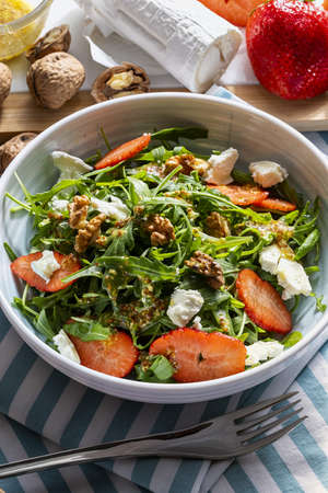 Vegetarian and healthy salad of green, natural, raw and freshly cut arugula (rugula) sprouts and leaves (brassicaceae), with fresh strawberries, walnuts, goat cheese and extra virgin olive oil. Mediterranean diet food.