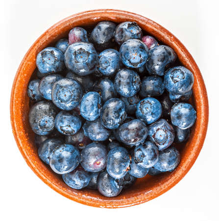 Fresh and raw blueberries with drops of water. In a clay bowl and ready to eat. Top view with copy space.