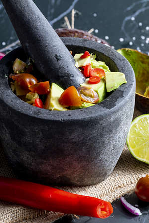 Preparation of guacamole in a traditional stone mortar with all its ingredients (chopped avocados, lime, onion, tomatoes and chili peppers). Appetizing and healthy traditional guacamole. Homemade look. Stock fotó