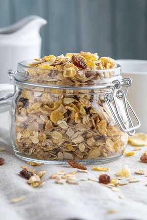 Glass jar with whole grains for breakfast. Muesli with dried fruits and dried fruits. With copy space.